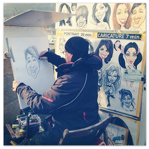 Художник рисует шаржи на Карловом мосту.