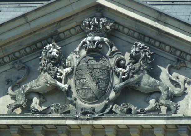 Львы держат герб с короной. Барельеф на фасаде здания под крышей.
