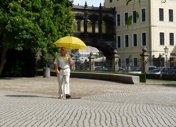 Одинокий мужчина под жёлтым зонтиком.