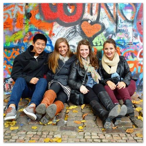 Студенты на фоне стены Джона Леннона.